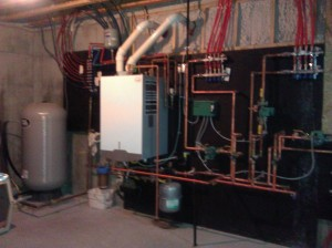 The Utility Room.  The grey tank in the left corner is our cistern.  An electric-powered pump draws the water from the well and directs it to the cistern.  The water is so pure and delicious!   The propane-powered furnace provides unlimited hot water on demand. The tubing leads to the radiant heat under the floor.