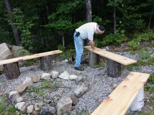My husband is drilling the hex bolts into the boards to secure the benches; while I'm busy swatting mosquitoes.