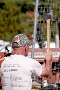 Both men and women entered the axe-throwing contest.  Here a man takes aim and is about to throw the axe toward the target.