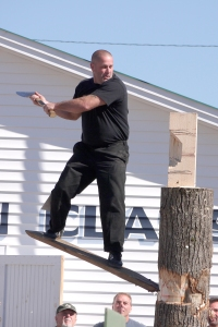 Once he gets to the top, a new challenge awaits:  he must chop a thick block of wood that is nailed to the top of the trunk in half.  This is much harder than it sounds:  he is now balanced precariously on the narrow plank of wood that he inserted into the gash on the trunk, while 12' - 14' above the ground!